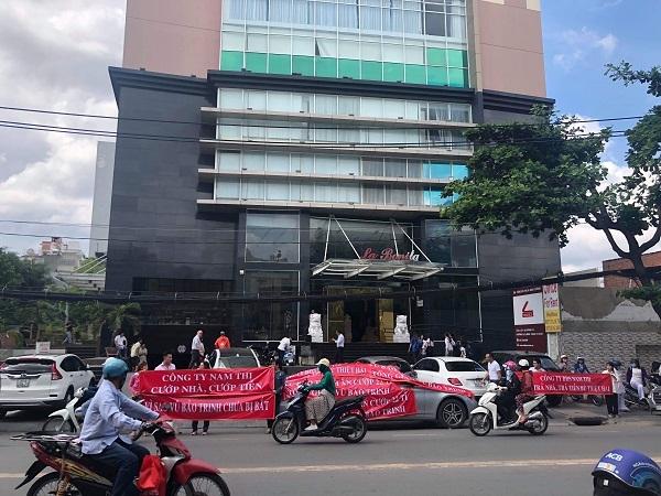 Đường phía trước một tòa nhà chung cư, nhiều người và xe qua lại, một số người căng băng rôn màu đỏ.