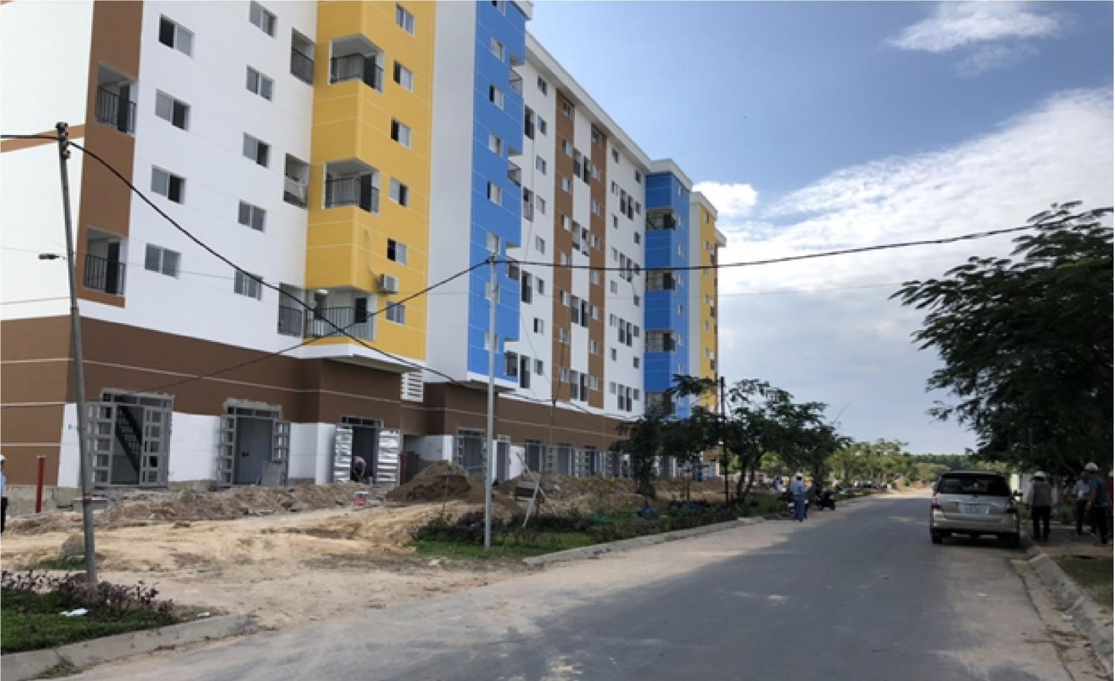 Một tòa chung cư nằm sát đường được sơn màu trắng, vàng, xanh