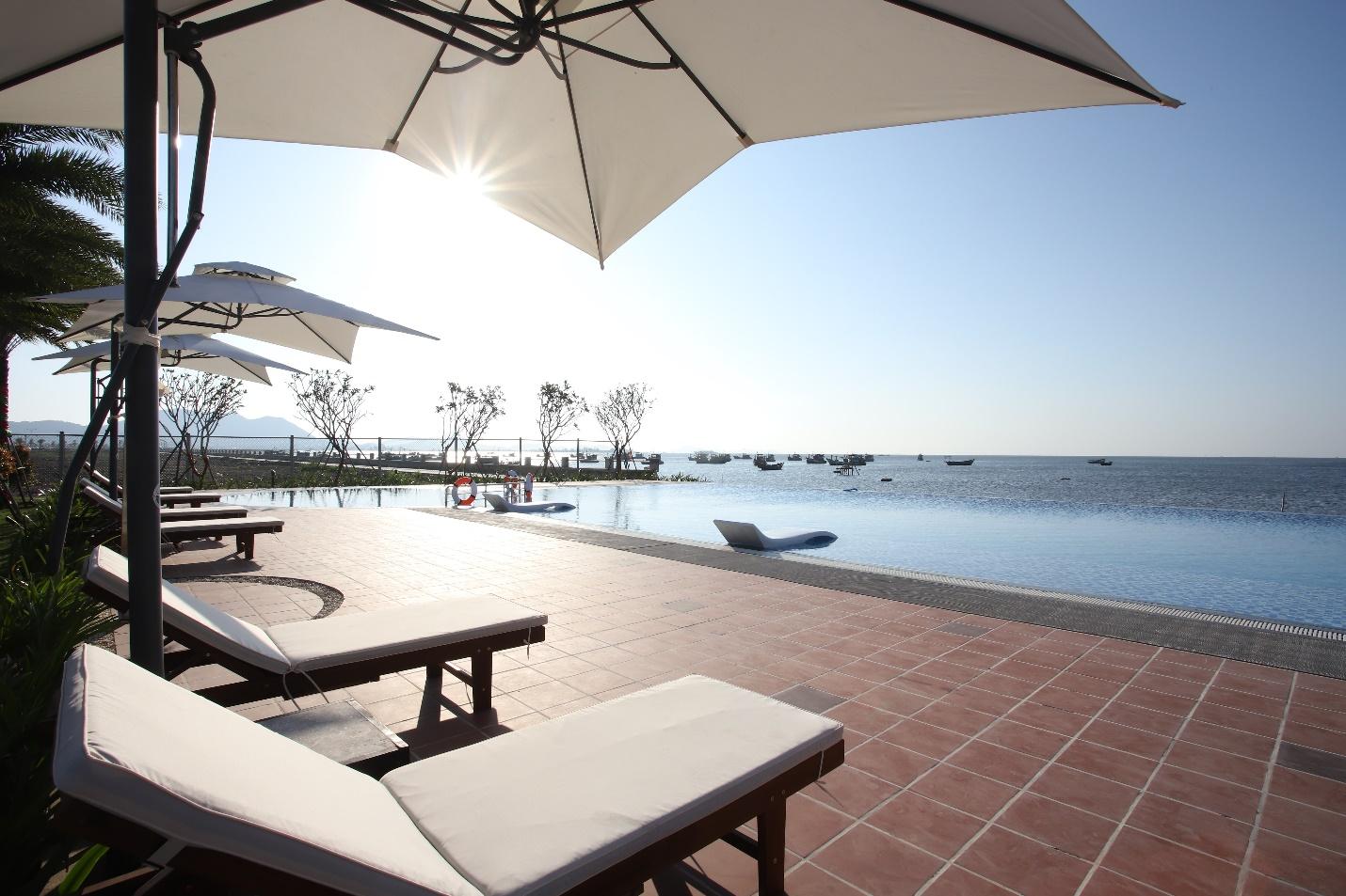 Một góc hồ bơi với chiếc ghế nằm thư giãn và ô che nắng