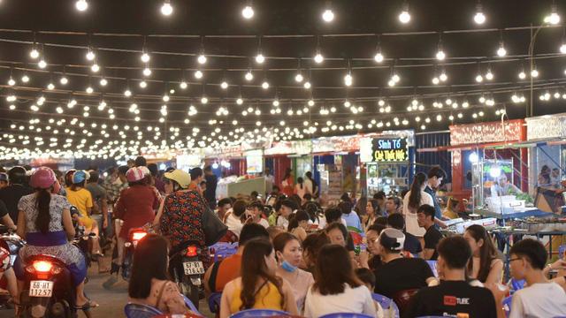 Một góc chợ đêm với đông người qua lại, ngồi ăn