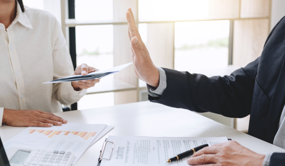 Trên bàn làm việc có giấy tờ và bút, người mặc vest giơ bàn tay tỏ ý không đồng ý với người mặc áo trắng đưa giấy tờ trước mặt.