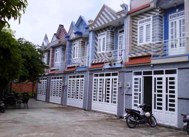 5 ngôi nhà 2 tầng nằm liền kề được mua bán qua vi bằng, phía trước có đường đi, một chiếc xe máy và cây cối