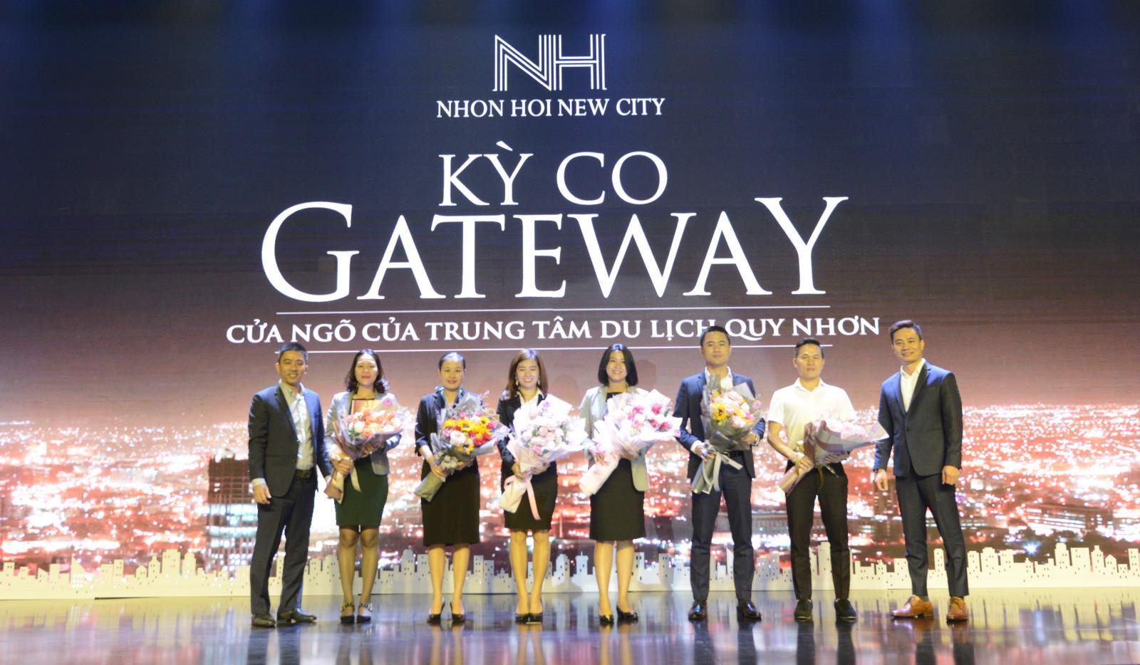 4 nam và 4 nữ đứng trên sân khấu ôm bó hoa