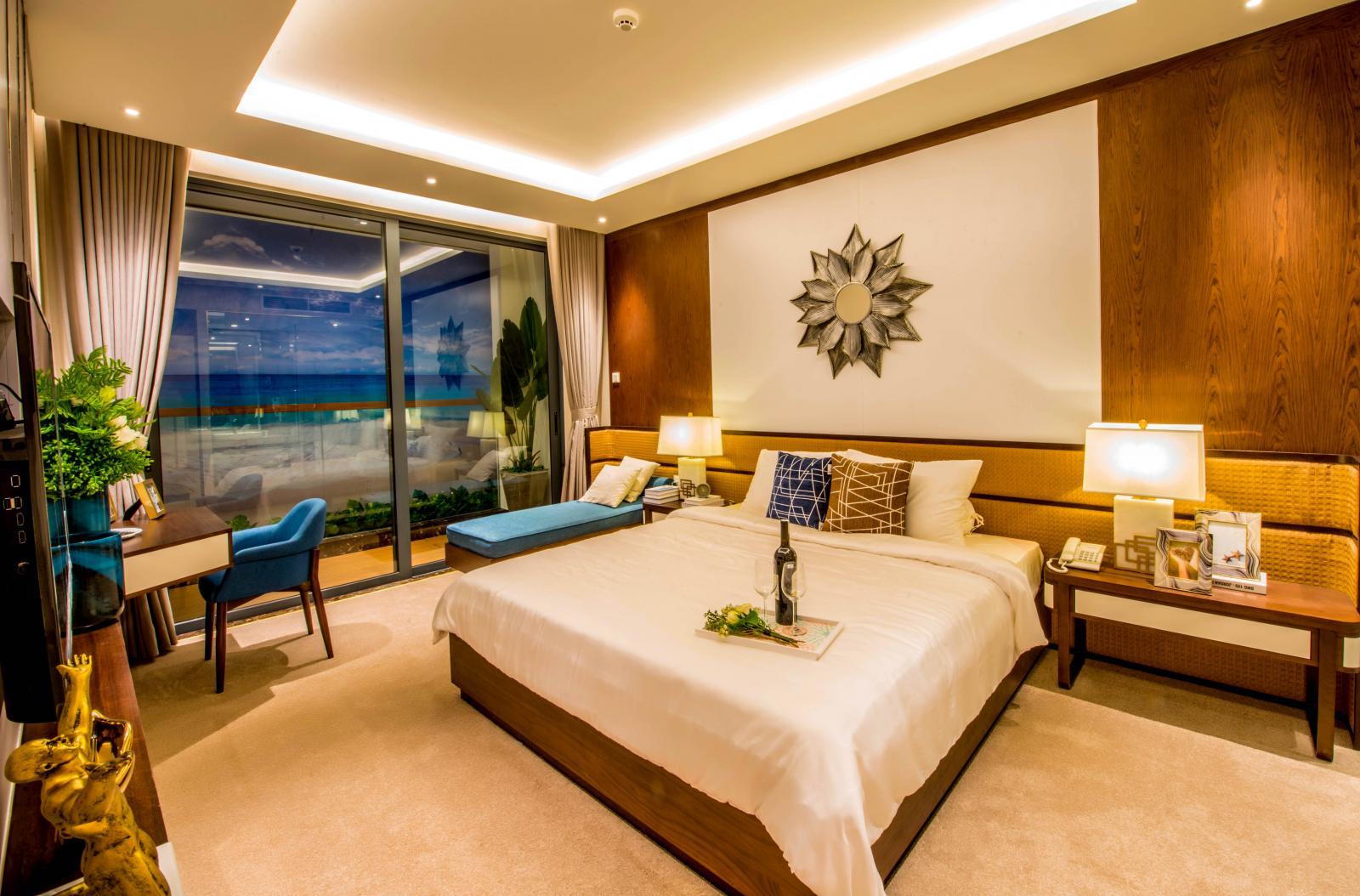 Một can phòng ngủ view biển với bộ ga giường màu trắng có chai rượu để trên giường,