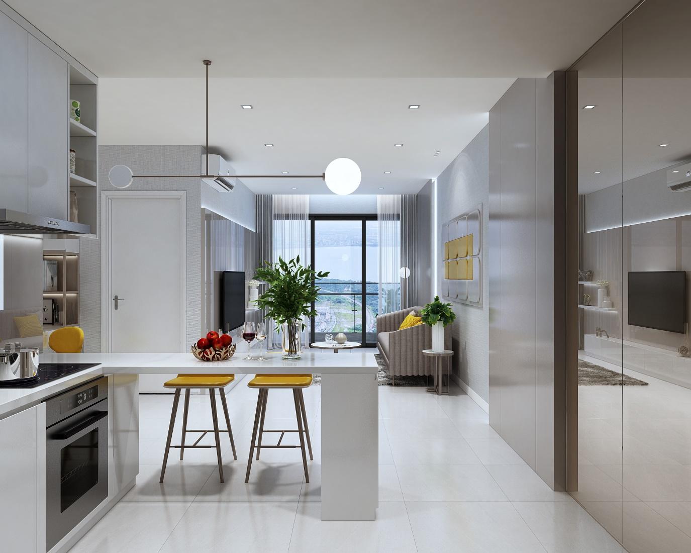 Căn hộ ricca màu trắng rộng rãi có phòng bếp với bộ bàn ghế, giỏ hoa quả nằm bên cạnh phòng khách có sofa và tivi