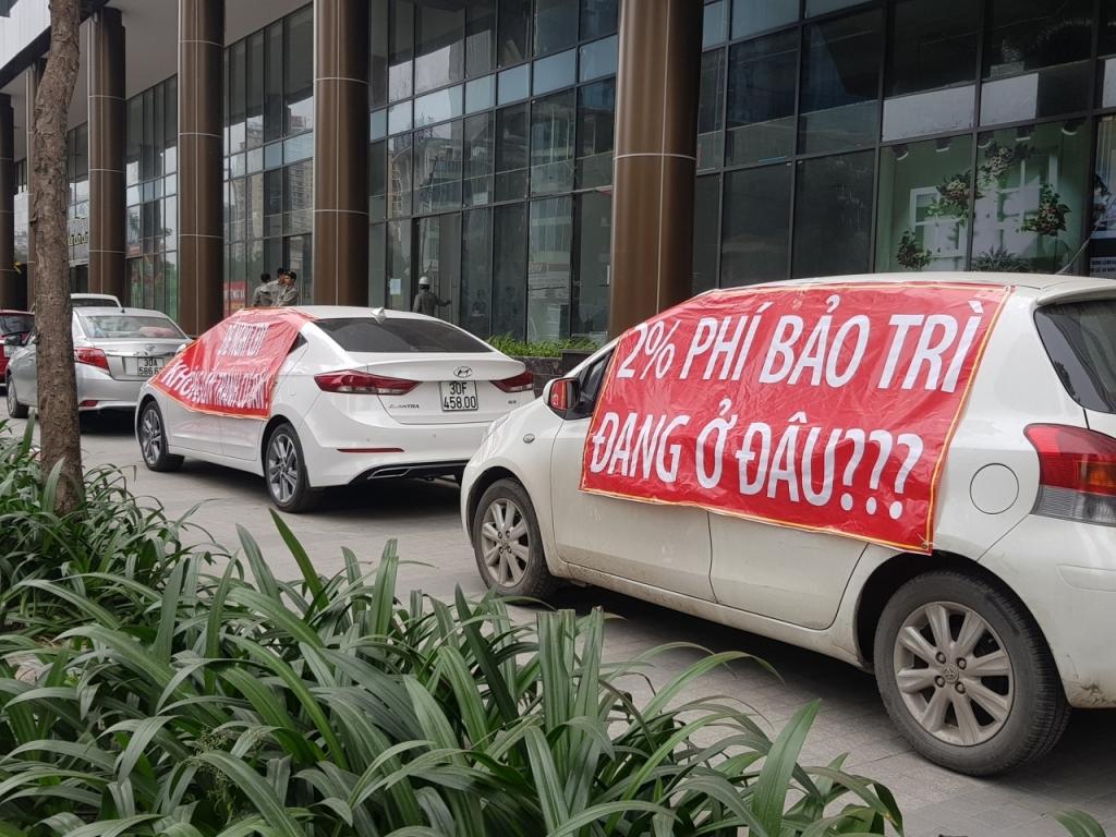 3 chiếc ô tô trắng căng băng rôn màu đỏ đỗ trước tòa nhà cao tầng để đòi phí bảo trì chung cư