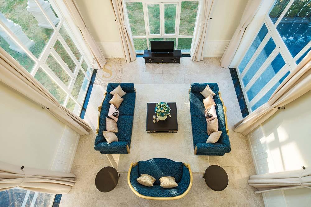 Ảnh chụp phòng khách từ trên cao với bộ sofa màu xanh, rèm cửa màu kem