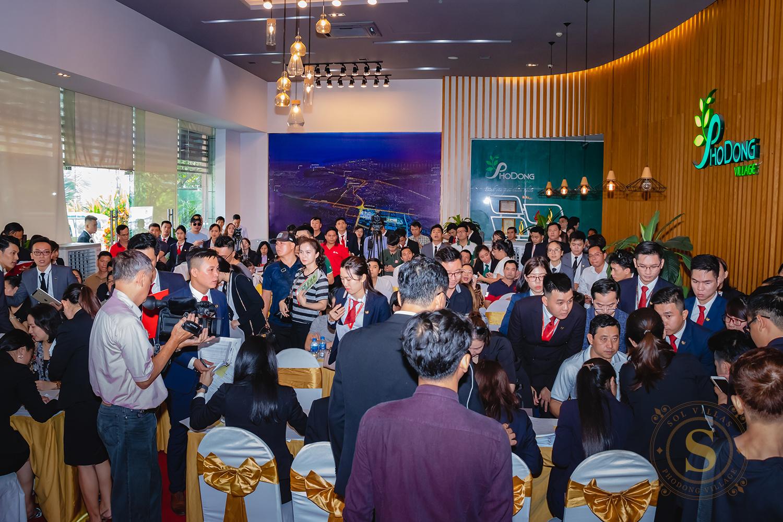 Nhiều người đứng, ngồi, chụp ảnh tại một sự kiện