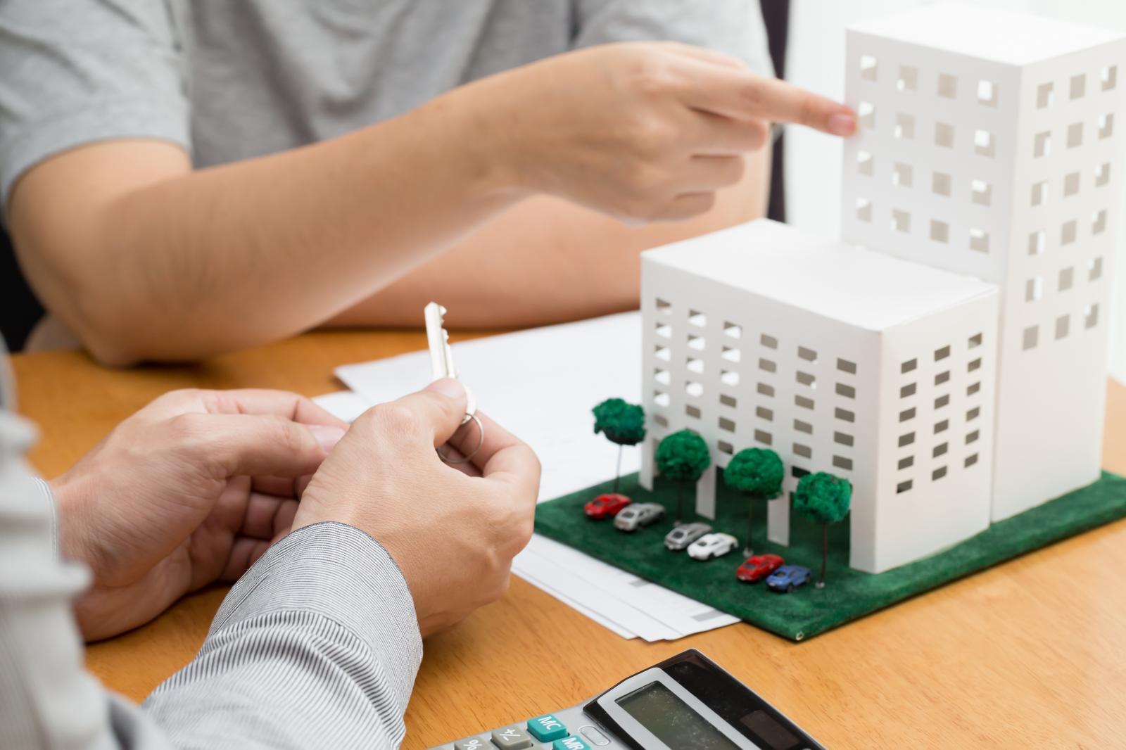 một bàn tay cầm chiếc chìa khóa, một bàn tay chỉ vào mô hình khu chung cư