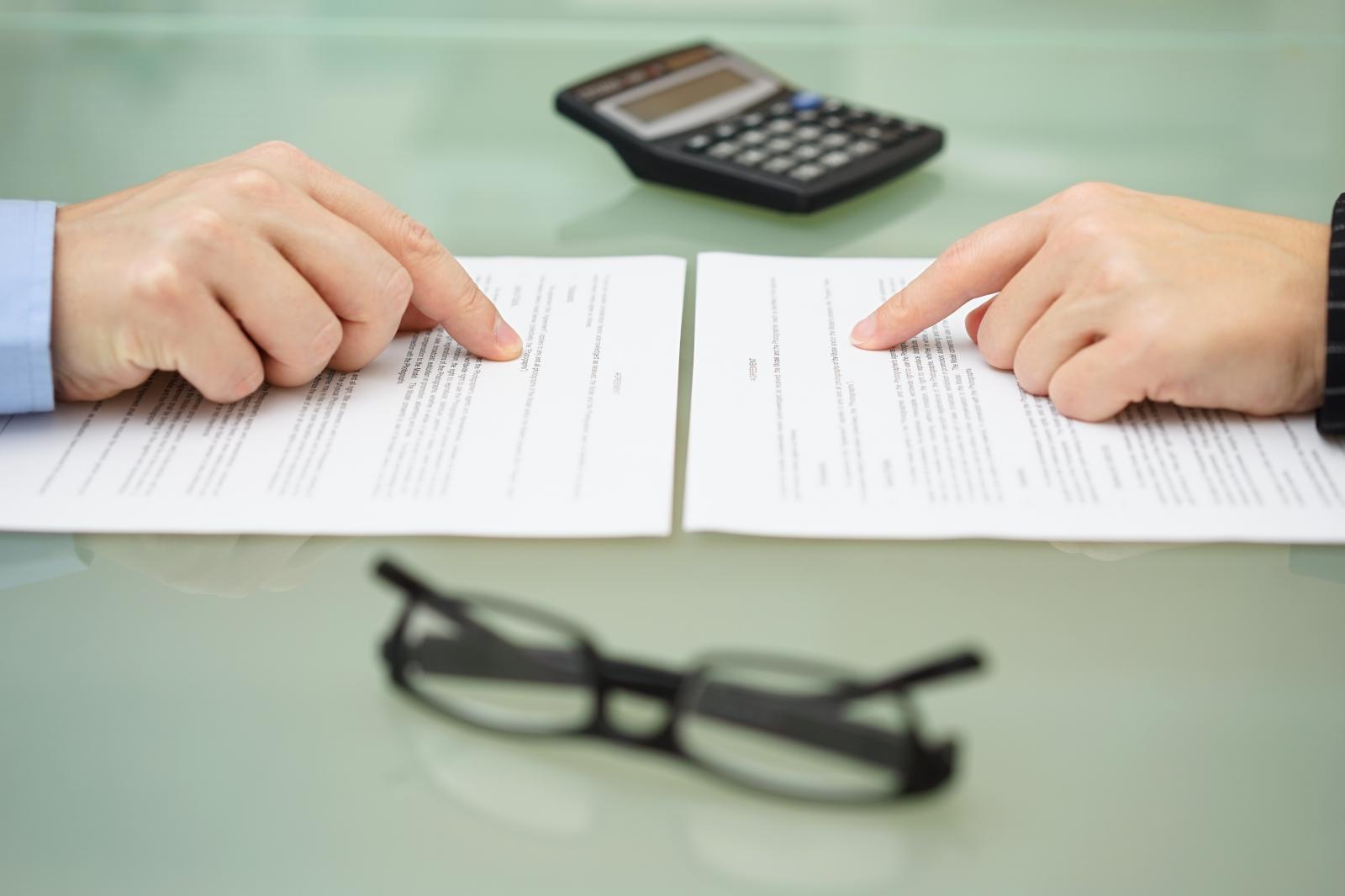 hai bàn tay đang chỉ vào tờ giấy để trên bàn