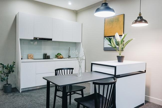 căn bếp màu trắng với hai chiếc đèn thả trần