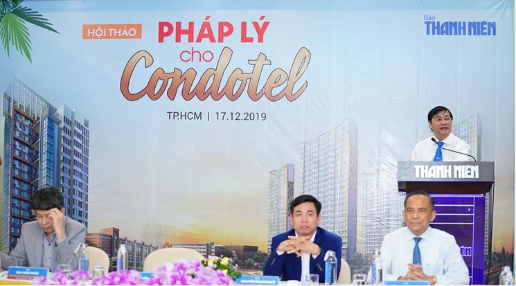 Ba người đàn ông luống tuổi ngồi trên bàn gần phông nền sân khấu, một người đứng trên bục phát biểu tại hội thảo về condotel.
