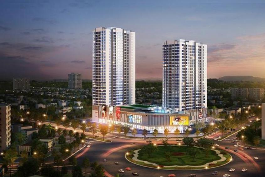 Phối cảnh hai tòa chung cư cao tầng giữa khu vực dân cư sầm uất, sáng đèn.