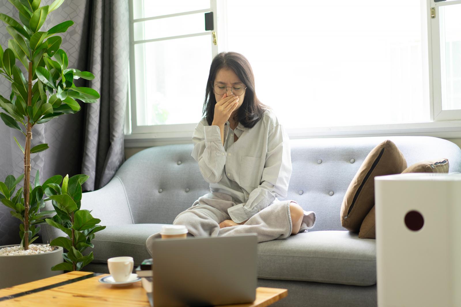 cô gái đang bịt mũi vì ô nhiễm không khí trong nhà