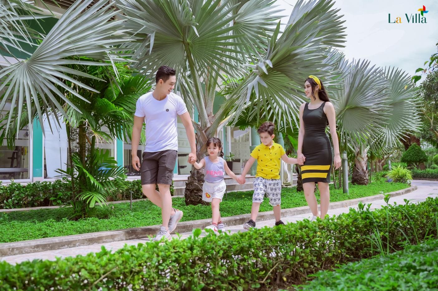 Một người đàn ông và một phụ nữ dắt tay một bé trai và một bé gái đi trong khuôn viên nhiều cây xanh