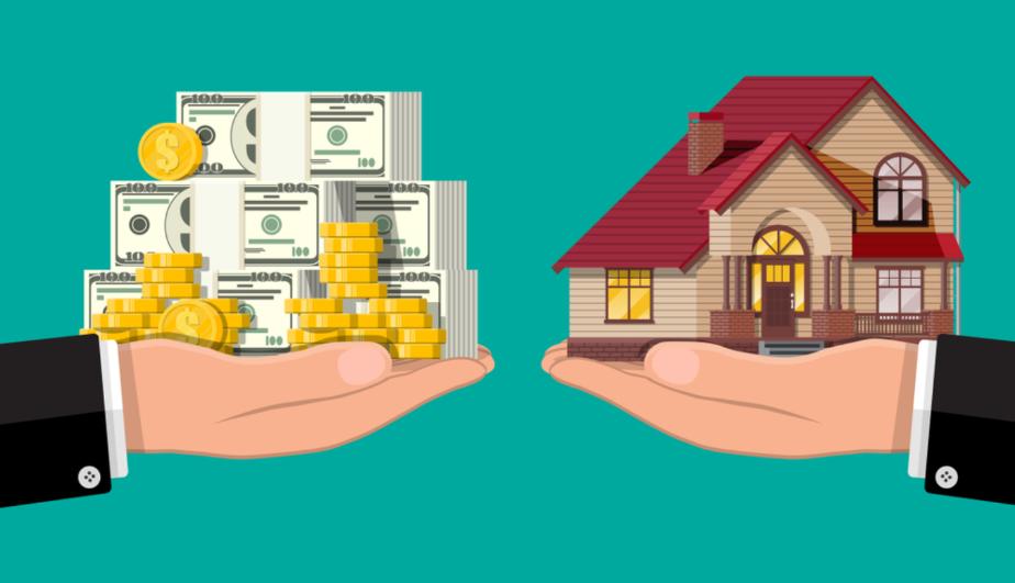 Một bàn tay cầm mô hình các cọc tiền và một tay cầm mô hình ngôi nhà trên nền màu xanh