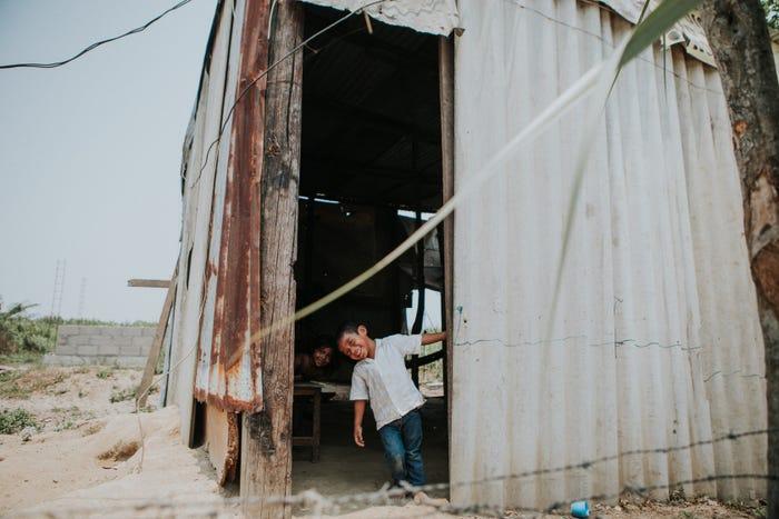đứa trẻ đang cười đùa trước cửa ngôi nhà bằng tôn xập xệ
