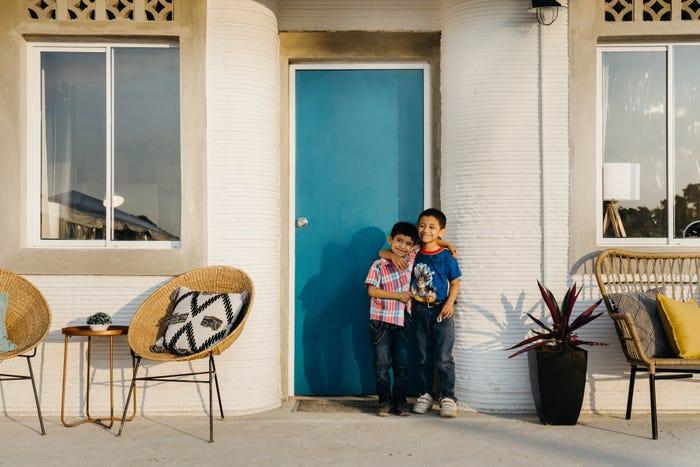 hai đứa trẻ đang ôm nhau trước cửa ngôi nhà in 3d