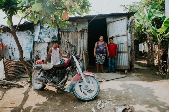 hình ảnh các thành viên trong gia đình đang đứng trước ngôi nhà tạm bằng tôn