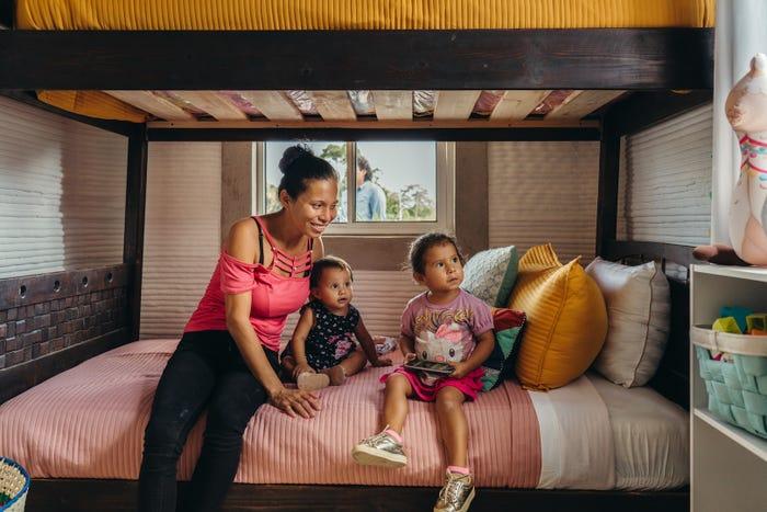 ba mẹ con đang ngồi trên giường trong ngôi nhà in 3d