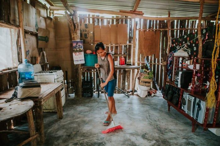 người phụ nữ đang quét nhà trong ngôi nhà tạm làm bằng gỗ và tôn