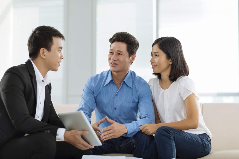 nhân viên môi giới bất động sản đang tư vấn cho khách hàng là cặp vợ chồng