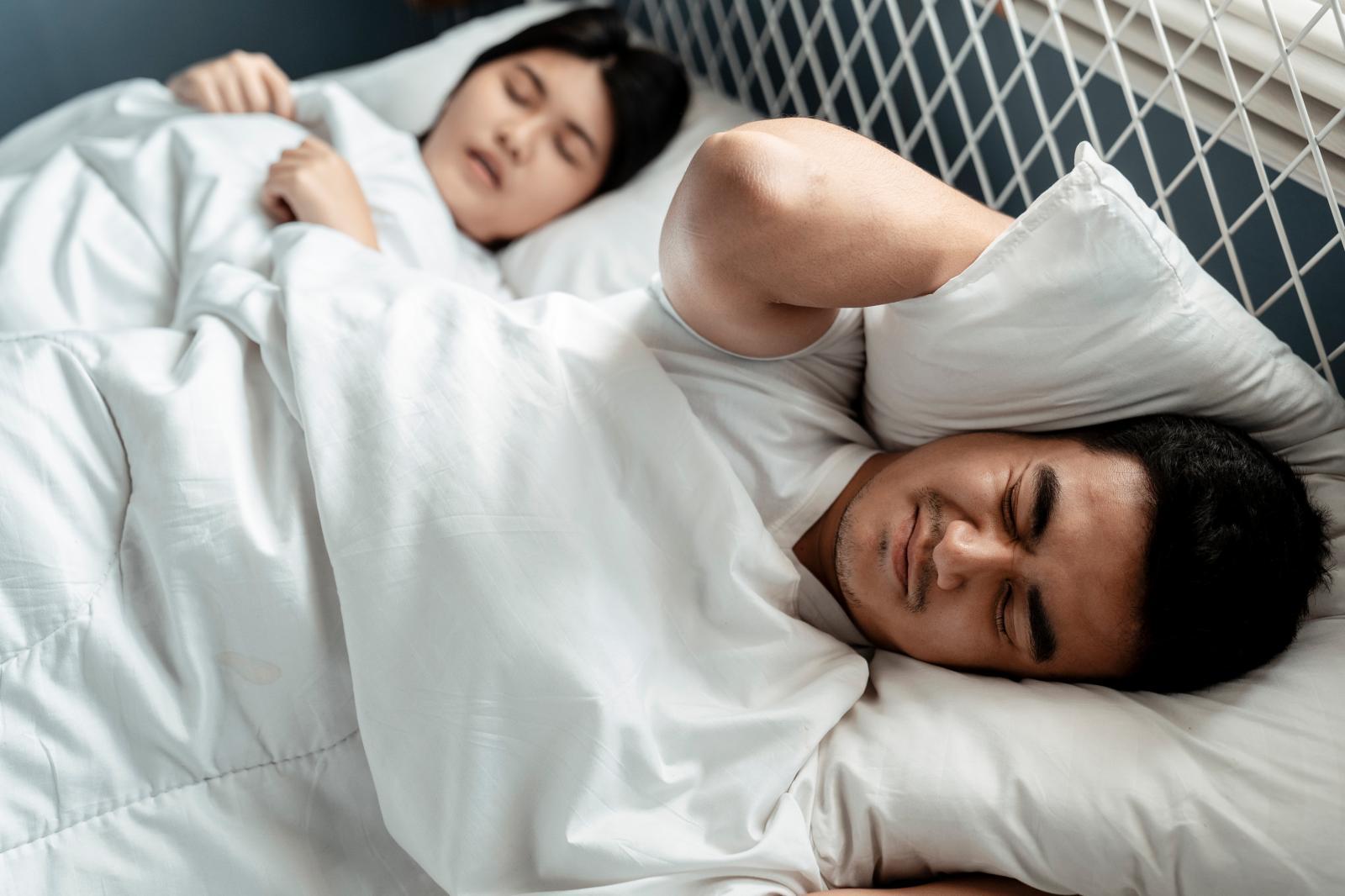 người đàn ông cau có, khó chịu  vì tiếng ồn khi đang nằm ngủ cạnh vợ