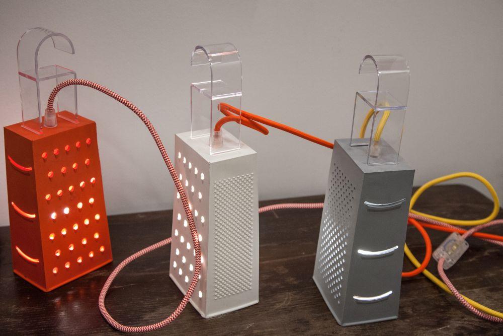 ba chiếc đèn nội thất màu cam, trắng, ghi xám có thiết kế giống dụng cụ bào rau củ