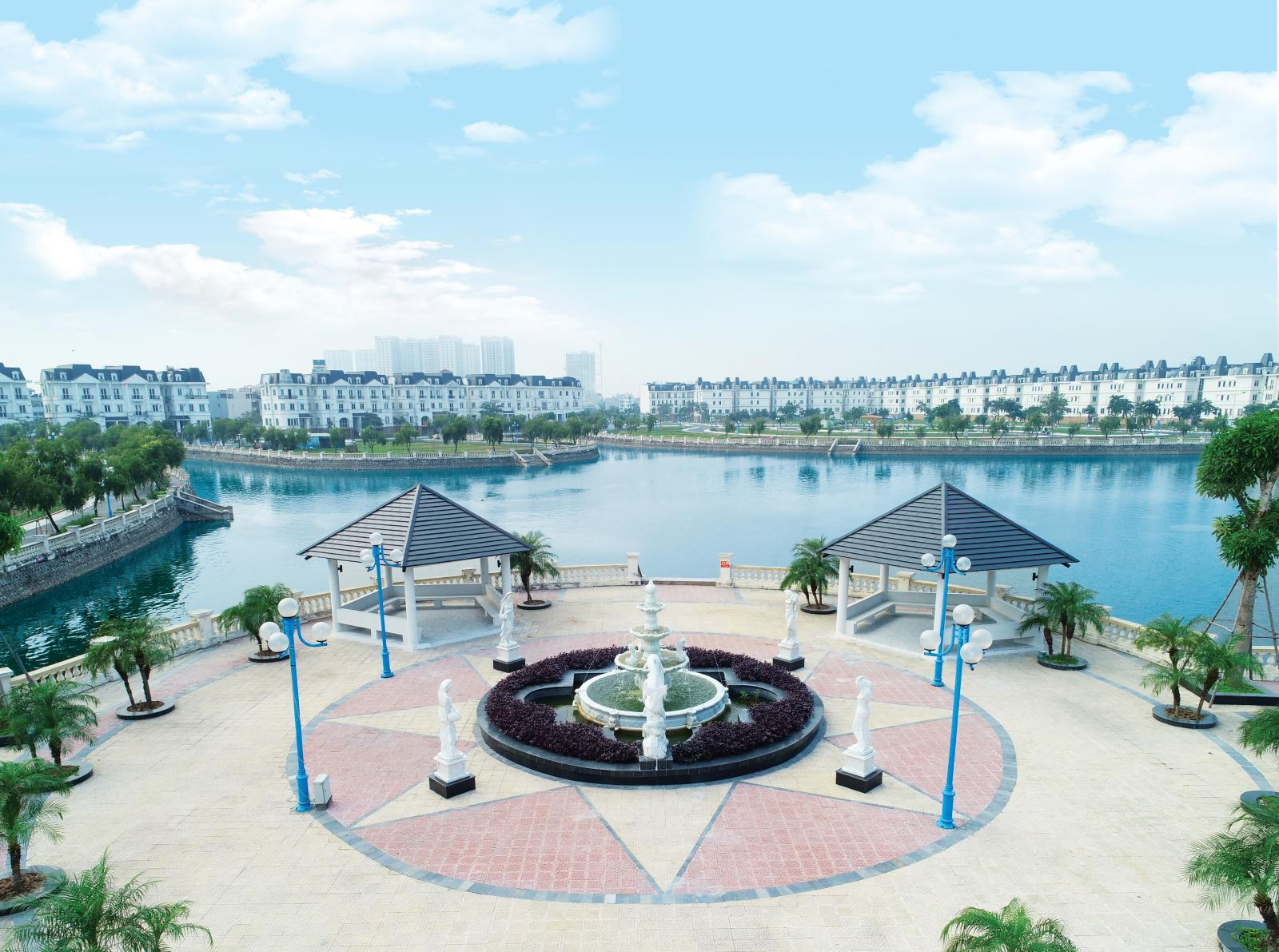 Đài phun nước hình tròn nằm sát hồ nước, xung quanh hồ là những dãy nhà biệt thự