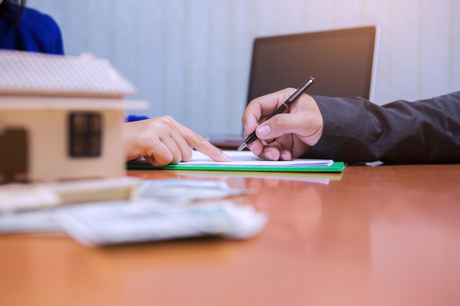 1 bàn tay cầm bút, 1 bàn tay chỉ vào tờ giấy trên bàn