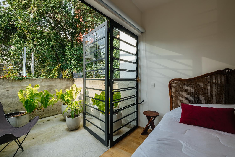 cửa kính khung thép trong phòng ngủ mở ra khoảng ban công
