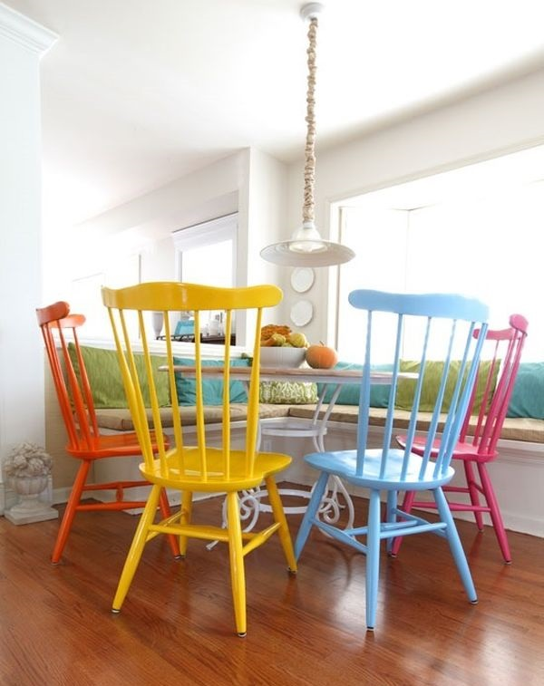 những chiếc ghế tựa sơn màu khác nhau đặt quanh bàn tròn