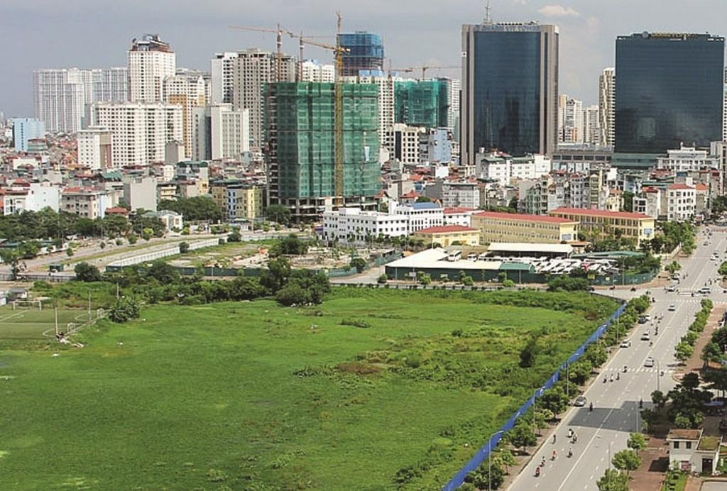 một khu đất trông, phía sau là nhiều tòa nhà cao tầng