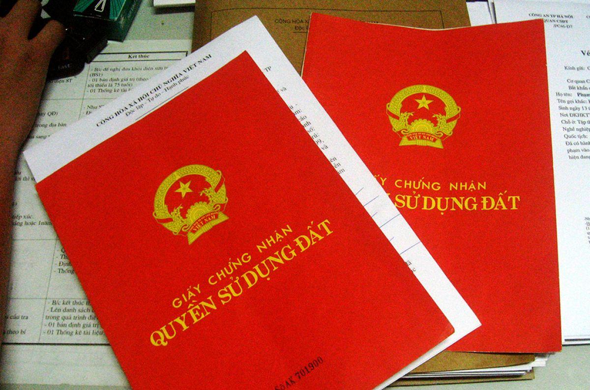 3 quyển sổ màu đỏ đặt trên bàn