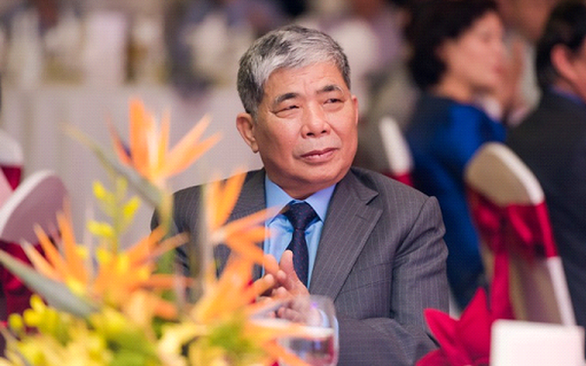 Chân dung một người đàn ông mặc vest, tóc bạc, ngồi cạnh lẵng hoa màu vàng.