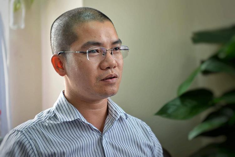 Chân dung một người đàn ông trẻ đầu trọc, đeo kính.
