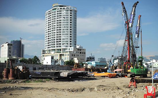 Khu đất trống ngổn ngang vật liệu, cẩu tháp, bên ngoài là những tòa nhà cao tầng.