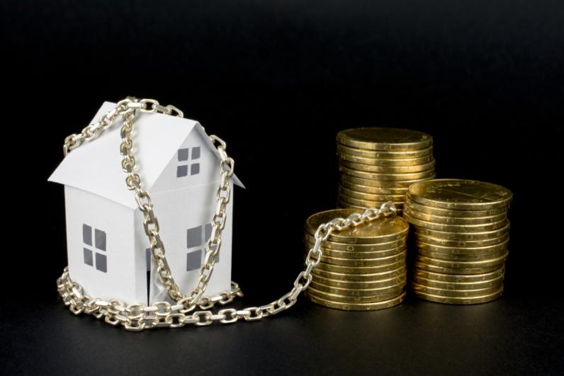 Trên phông nền đen, mô hình một ngôi nhà màu trắng bị sợi xích bao quanh, bên cạnh là các cọc tiền xu