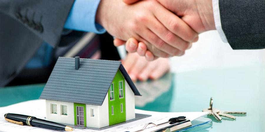 hai bàn tay đang bắt tay nhau, một cái bút và một mô hình ngôi nhà đặt trên bàn