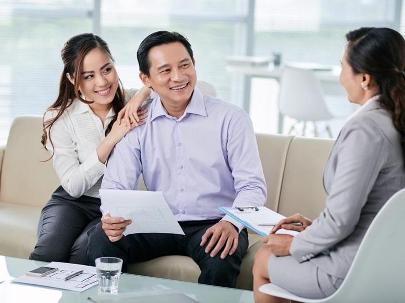 1 người đàn ông và 2 người phụ nữ đang nói chuyện, trên bàn có cốc nước và nhiều giấy tờ