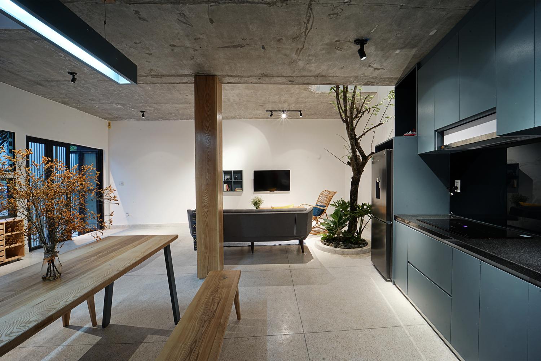 hệ tủ bếp màu xanh dương bắt mắt, cạnh đó là bàn ăn kết hợp băng ghế