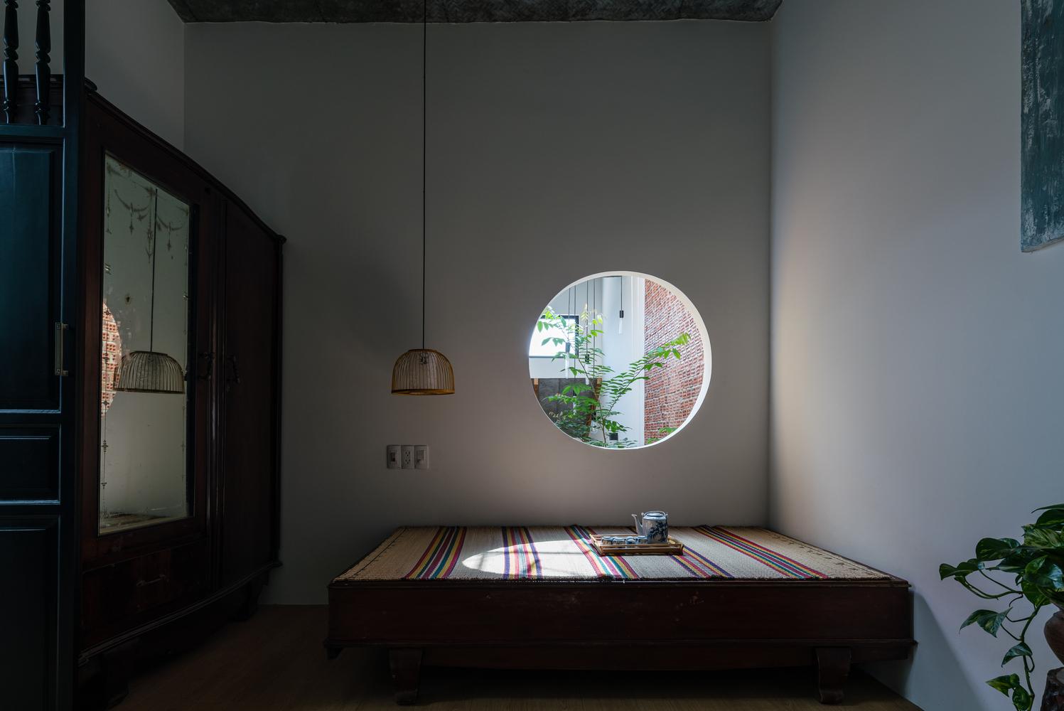 phòng ngủ có ô thoáng hình tròn mở ra khoảng giếng trời