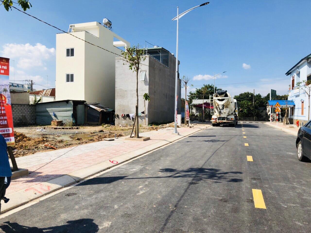 Con đường lớn mới làm, vỉa hè, xung quanh là một số ngôi nhà.