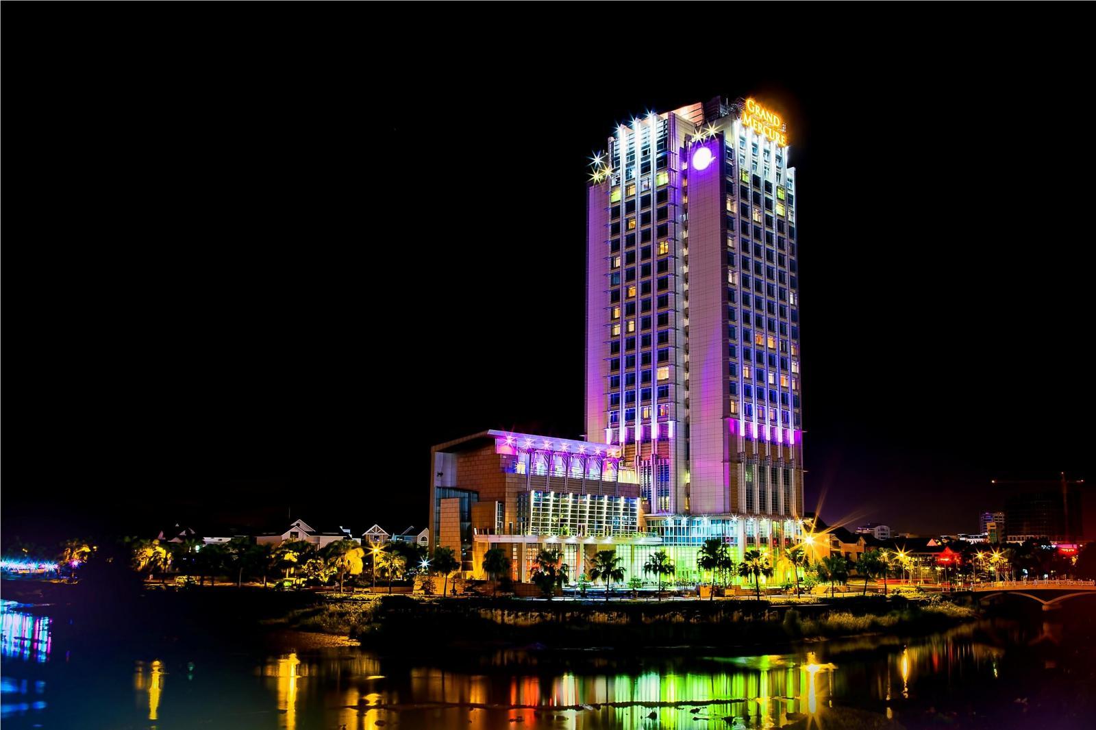 tòa nhà cao tầng nằm ven sông vào ban đêm