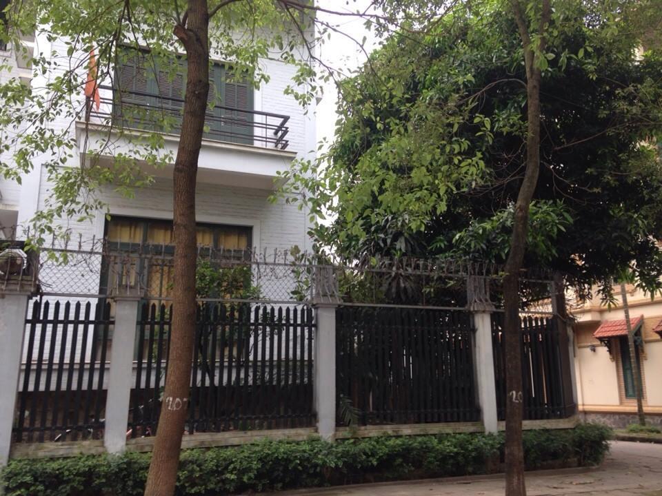 Ảnh chụp phía ngoài một căn biệt thự màu trắng, hàng rào bao quanh, cây lớn ngoài vỉa hè.