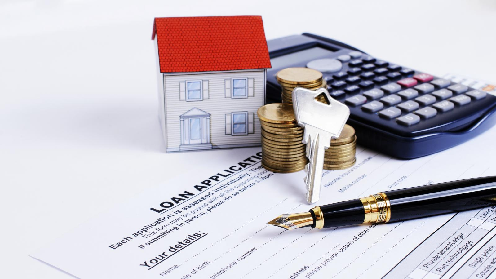 Hình ảnh ngôi nhà, giấy bút, chiếc máy tính cầm tay và đồng tiền xu