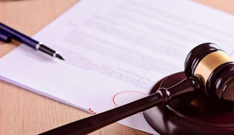 một cái bút, một tờ giấy và biểu tượng chiếc búa của ngành luật đặt trên bàn