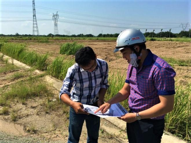 hai người đàn ông trẻ đứng xem bản đồ giữa một khu đất rộng lớn