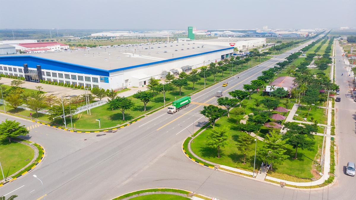 Khu kho xưởng lớn nằm cạnh con đường nhiều cây xanh.