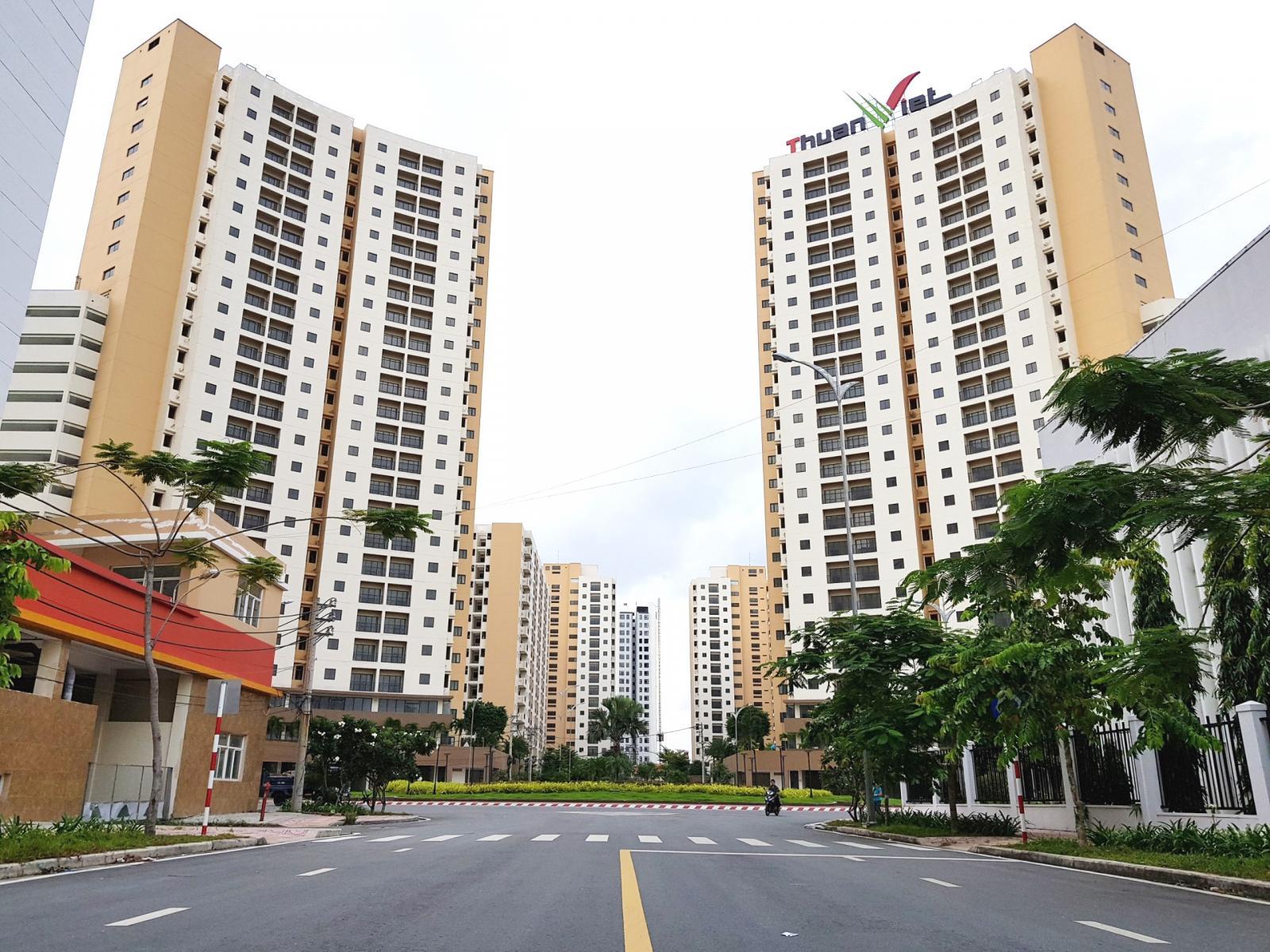 Khu dự án nhà giá rẻ gồm nhiều tòa nhà cao tầng màu trắng - vàng, bên dưới  là đường và nhiều cây xanh.